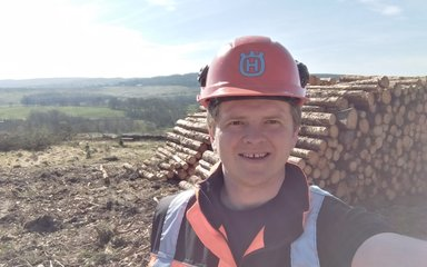Forester taking selfie in front of a timber stack