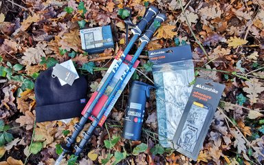 Hat, binoculars, walking poles, water bottle, map case and a compass on the forest floor