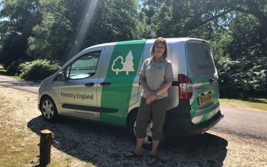 Forestry England staff member stood next to van on sunny day