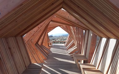 View through a striking timber shelter structure with view in the distance