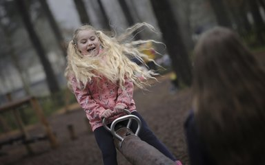 girl playing on a see-saw in the forest