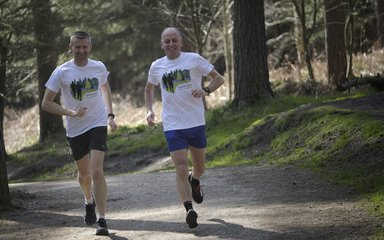 Two men running in the forest
