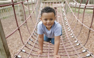 Child playing on rope bridge