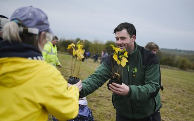 Forestry England worker handing small tree to women in yellow coat