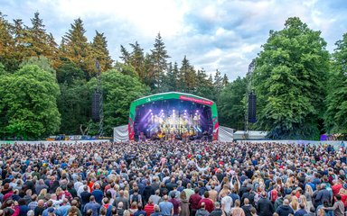 Forest Live stage surrounded by trees and showing a large crowd.