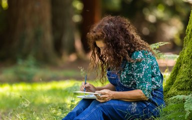 Woman sat at the base of a mossy tree drawing in a notebook