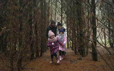 Family running through lines of bare trees in winter