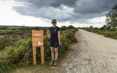 Recreation ranger Amy Howell standing next to a sign about nesting birds in the New Forest