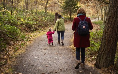 Mother and child walking on forest path during autumn