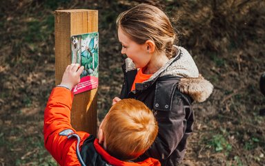Two children looking at a gruffalo orienteering marker post