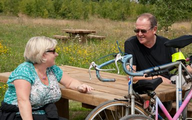 middle aged couple with bicycles by a picnic bench
