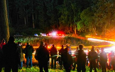 A blur of lights beyond a group of spectators at night rally