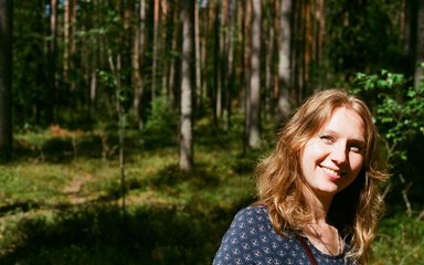 Fair haired woman smiles in the sunlight, with a forest backdrop