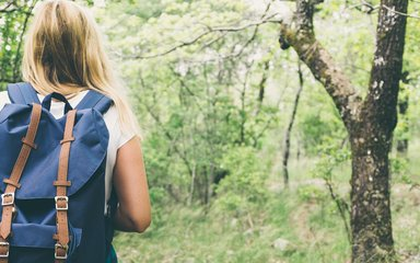 Women with blue backpack walking through spring woodland
