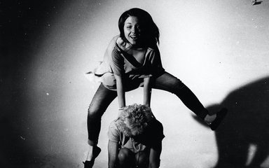 Black and white photo of girl leap-frog jumping over someone's back
