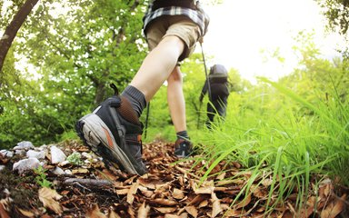 Close up of walking boots of person walking along a leafy path