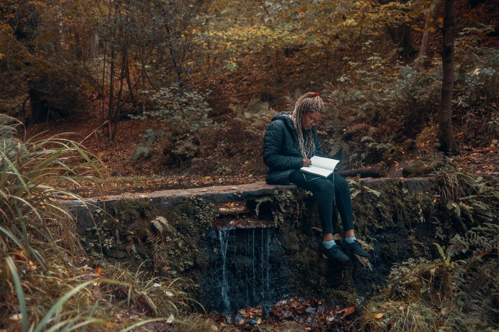 Woman writing in a notepad by a pond