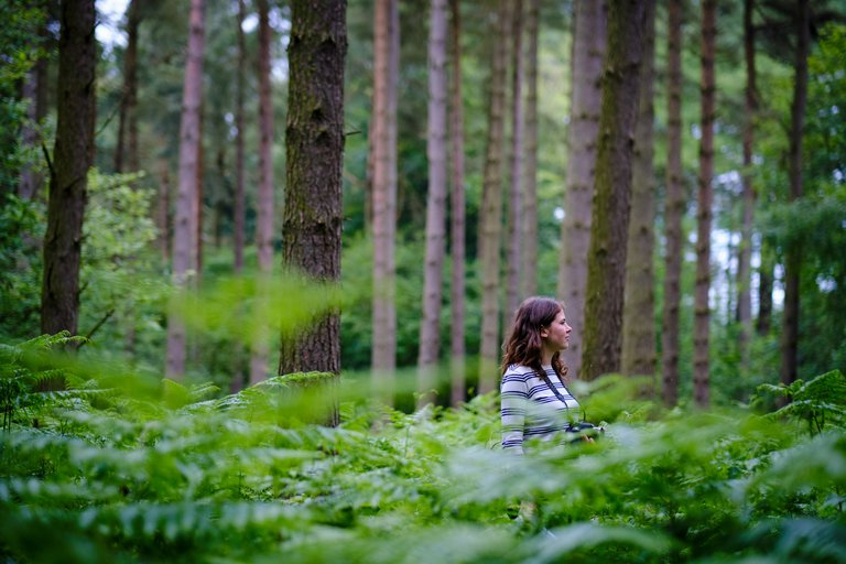 Woman stood amongst large leaves in the forest