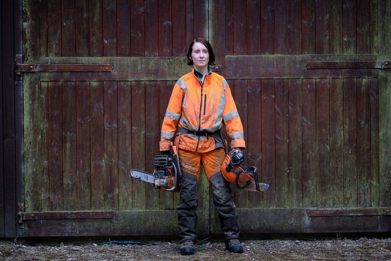 Female forester with chainsaw stood in front of wooden doors
