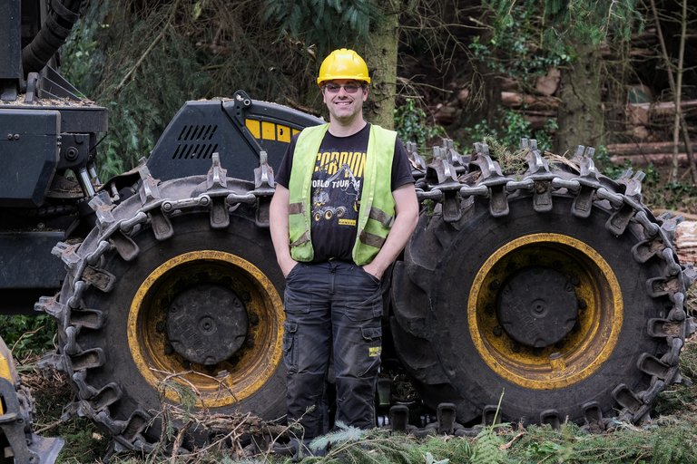 Forester stood in front of forestry machine in high vis and hard hat