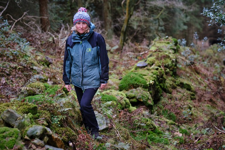 Woman stood on mossy rocks in the rich forest