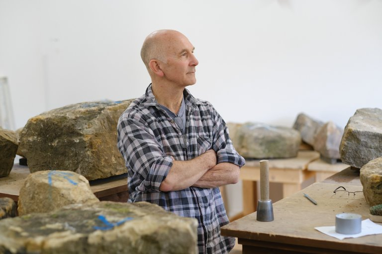 Man stood with folded arms surrounded by giant rocks in a workshop